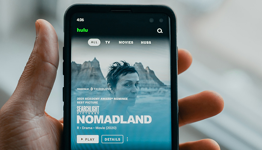 Holding a phone with Hulu on the screen