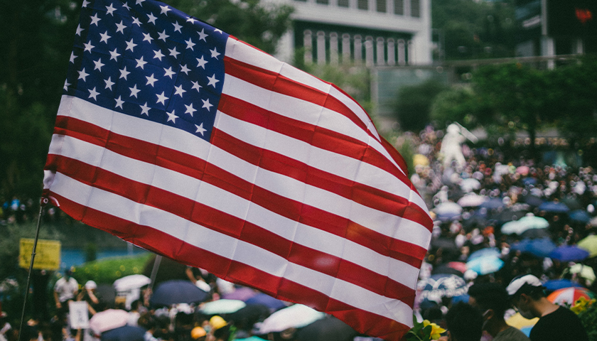 American flag in front of large crowd of people