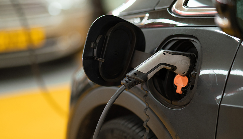Black, electric car being charged at charging station