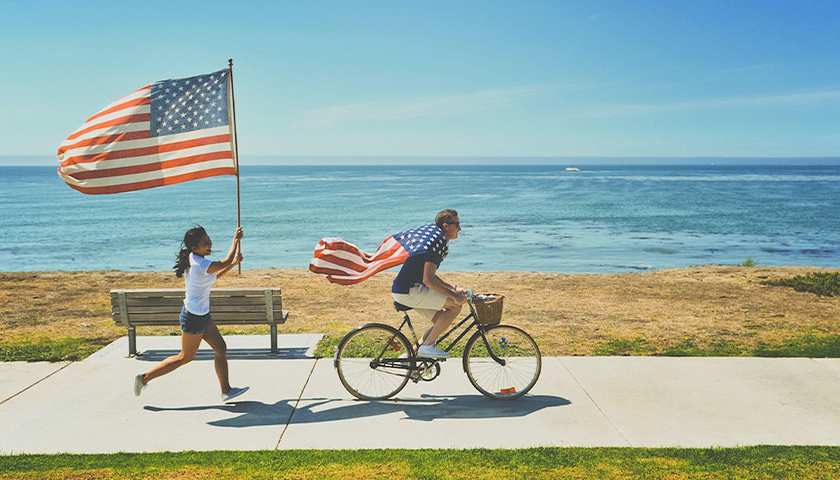 Person running with American flag behind person riding bike with American flag as cape