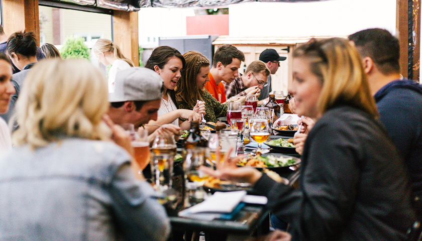 Group of people sitting at public restaurant, eating.