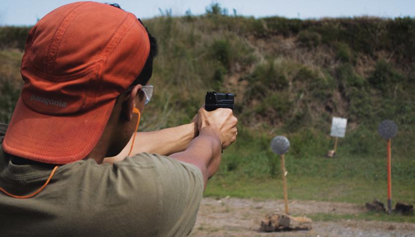 Guy shooting hand gun at gun range