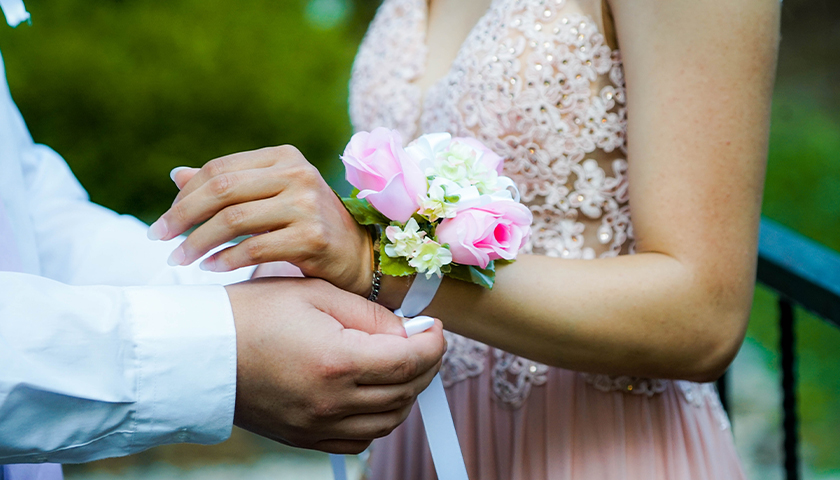 Boy putting on a corsage on woman's wrist