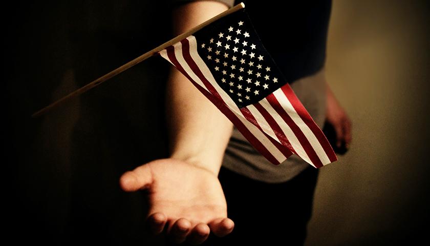 Hand underneath American flag