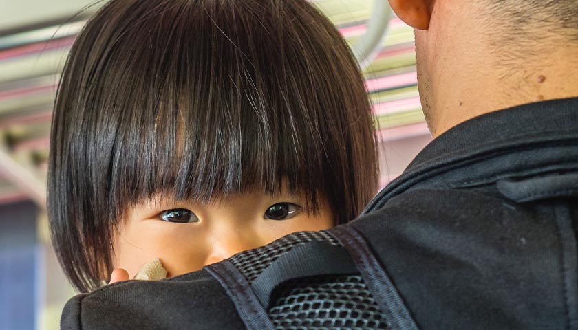 Chinese child being held, peaking over shoulder of dad