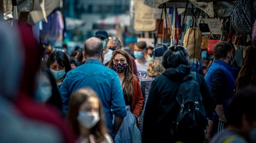 Crowded street market with people wearing masks