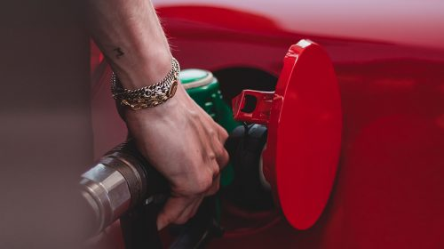 Person filling up red car with petrol/gasoline